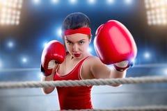 Kvinnlig boxare i röda boxninghandskar på cirkeln royaltyfri foto