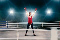 Kvinnlig boxare i röda sportswearhänder upp på cirkeln arkivbilder
