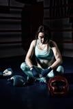 Kvinnlig boxare som sitter nära liggande boxninghandskar och hjälm Royaltyfri Fotografi