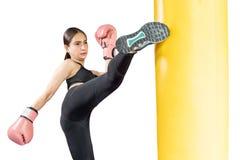 Kvinnlig boxare som slår en enorm stansa påse på en boxningstudio Kvinnaboxare som hårt utbildar Thailändsk boxarestansmaskinspar arkivbilder