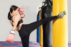 Kvinnlig boxare som slår en enorm stansa påse på en boxningstudio Kvinnaboxare som hårt utbildar Thailändsk boxarestansmaskinspar royaltyfri foto