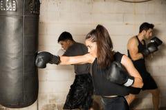 Kvinnlig boxareutbildning i en idrottshall Arkivbilder
