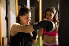 Kvinnlig boxareutbildning i en idrottshall royaltyfri foto