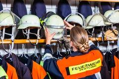 Kvinnlig brandkämpe i omklädningsrummet med låsbara skåp som tar hjälmen arkivbilder