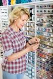 Kvinnlig bredvid hylla med knappar Fotografering för Bildbyråer
