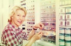 Kvinnlig bredvid hylla med knappar Arkivbilder
