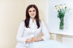 Kvinnlig brunettcosmetologist i likformig nära fönstret i cosmetologykontoret arkivfoton