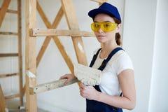 Kvinnlig byggmästare Doing Plaster Works Arkivbilder