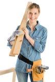 Kvinnlig byggnadsarbetare Carrying Wooden Plank på skuldra Royaltyfri Bild