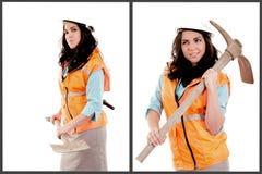 Kvinnlig byggnadsarbetare som poserar med hackayxan arkivbild