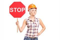 Kvinnlig byggnadsarbetare som rymmer ett stopptecken Royaltyfri Bild