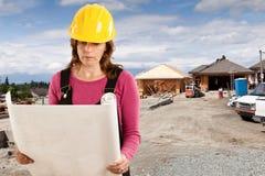 Kvinnlig byggnadsarbetare som ser plan på en ny hem- constr Royaltyfri Bild