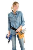 Kvinnlig byggnadsarbetare With Tool Belt och drillborr som bort ser royaltyfria bilder