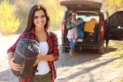 Kvinnlig campare med sovsäcken nära bilen utomhus arkivbild