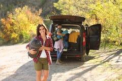 Kvinnlig campare med sovsäcken nära bilen utomhus royaltyfria foton