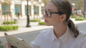 Kvinnlig caucasian student i utomhus- kafé med tidningen arkivfilmer
