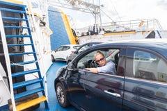 Kvinnlig chaufför som parkerar hennes bil på färjan på tur till deras destination för ö för sommarsemestrar Sardinia Italien royaltyfria bilder