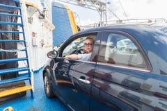 Kvinnlig chaufför som parkerar hennes bil på färjan på tur till deras destination för ö för sommarsemestrar Sardinia Italien arkivbilder