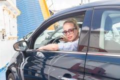 Kvinnlig chaufför som parkerar hennes bil på färjan på tur till deras destination för ö för sommarsemestrar Sardinia Italien fotografering för bildbyråer