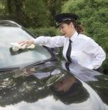 Kvinnlig chaufförlokalvårdvindruta av bilen Arkivfoto