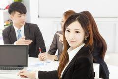 Kvinnlig chef för affär med lag i kontoret Arkivfoton