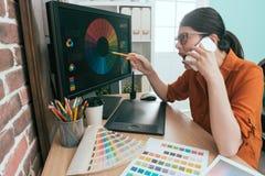 Kvinnlig chef som arbetar på företaget för grafisk design Fotografering för Bildbyråer