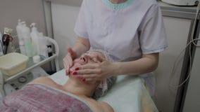 Kvinnlig cosmetologist som gör framsidamassage till den äldre kvinnan i cosmetological klinik lager videofilmer