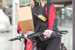 Kvinnlig cyklist med kartongen och kuriren Bag Royaltyfri Bild