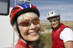 Kvinnlig cyklist med mannen i bakgrunden Arkivbild