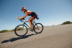 Kvinnlig cyklist på en landsväg Fotografering för Bildbyråer