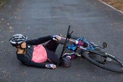 Kvinnlig cyklist som är stupad från hans mountainbike Arkivbilder