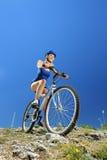 Kvinnlig cyklist som cyklar en mountainbike arkivfoto