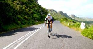 Kvinnlig cyklist som cyklar på en bygdväg bredvid ett frodigt berg 4k arkivfilmer