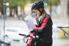 Kvinnlig cyklist som sätter packen i kuriren Bag Arkivfoto