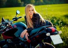 Kvinnlig cyklistflicka för sexigt mode Blond kvinna i sammanträde för läderomslag på tappningegenmotorcykeln Utomhus livsstil fotografering för bildbyråer