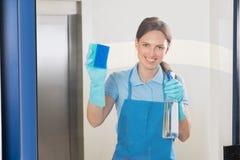 Kvinnlig dörrvakt Cleaning Glass royaltyfria bilder