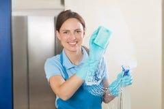 Kvinnlig dörrvakt Cleaning Glass arkivfoto