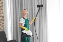 Kvinnlig dörrvakt som tar bort damm från gardinen med ångarengöringsmedlet arkivfoton