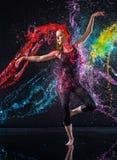 Kvinnlig dansare Being Splashed med färgrikt vatten Fotografering för Bildbyråer