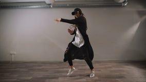 Kvinnlig dansare i den vita skjortan, svart byxa och svarta locket som visar modern jazz-fegis dans i klassrum med speglar arkivfilmer