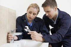 Kvinnlig deltagare i utbildningrörmokare Working On Tap i badrum Arkivfoton