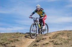 Kvinnlig deltagare som cyklar ner över kullen under det första loppet för amatör`-vår av en lokal cykelklubba i Dnipr Royaltyfria Foton