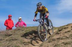 Kvinnlig deltagare som cyklar ner över kullen under det första loppet för amatör`-vår av en lokal cykelklubba i Dnipro Royaltyfria Bilder