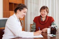 Kvinnlig doktor av att ordinera till den mogna patienten läkarbehandlingen Arkivbild