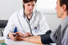 Kvinnlig doktor Checking Blood Pressure av tålmodign royaltyfria foton