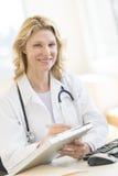 Kvinnlig doktor With Clipboard Sitting på skrivbordet i klinik Arkivfoto