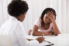 Kvinnlig doktor Comforting Depressed Patient royaltyfri fotografi