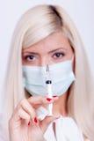 Kvinnlig doktor eller sjuksköterska i medicinsk maskeringsinnehavinjektionsspruta med inje Arkivfoto