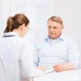 Kvinnlig doktor eller sjuksköterska med gamala mannen som prescrbing Arkivbilder