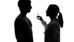 Kvinnlig doktor eller sjuksköterska som ger injektionen eller vaccinen till den manliga patienten, hälsa fotografering för bildbyråer